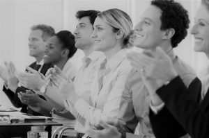 Happy Group Of Businesspeople Clapping In Boardroom